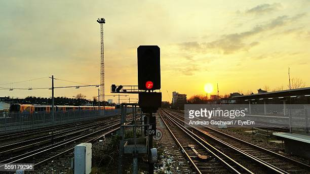 railroad tracks and signal during dusk - red light stock pictures, royalty-free photos & images