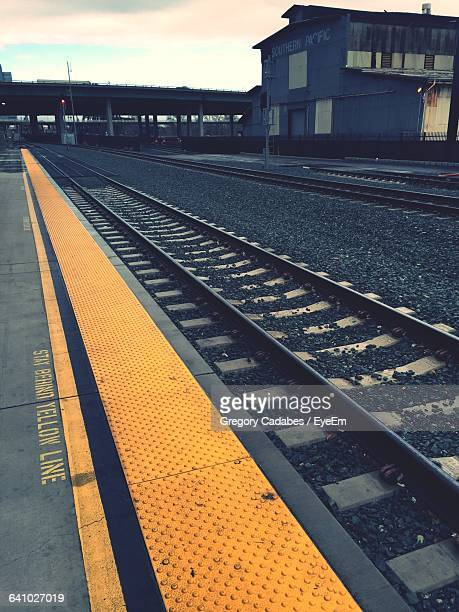 railroad tracks at station at dusk - double yellow line stock photos and pictures