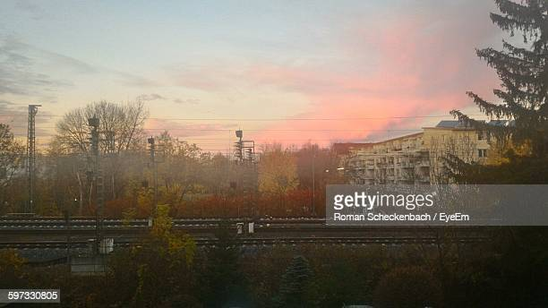 Railroad Tracks By Buildings Against Sky During Sunset