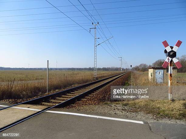 railroad tracks by field against clear sky - railroad crossing stock pictures, royalty-free photos & images