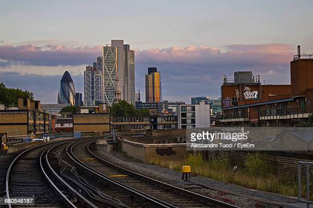 Railroad Tracks By Modern Buildings Against Sky During Sunset