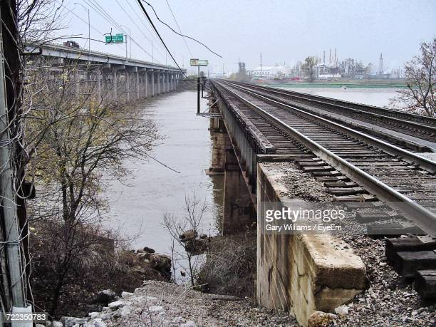 railroad tracks by river in city against sky - tulsa stock pictures, royalty-free photos & images