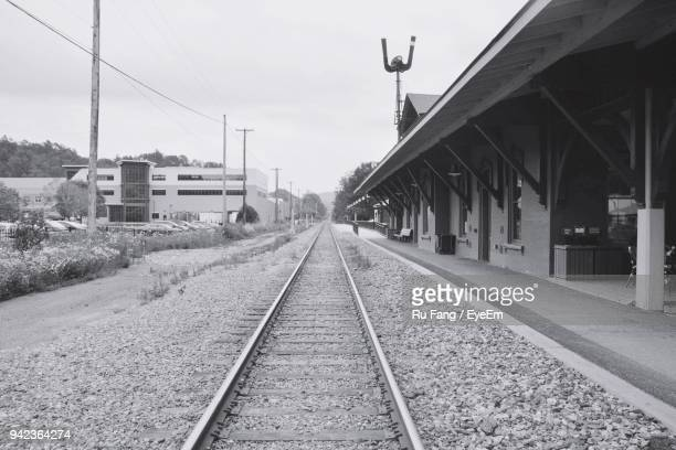 Railroad Tracks By Station Against Sky