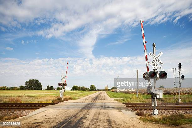 railroad tracks crossing country road - railroad crossing stock pictures, royalty-free photos & images