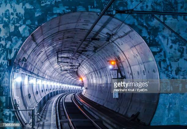 Railroad Tracks Leading To Illuminated Tunnel At Night