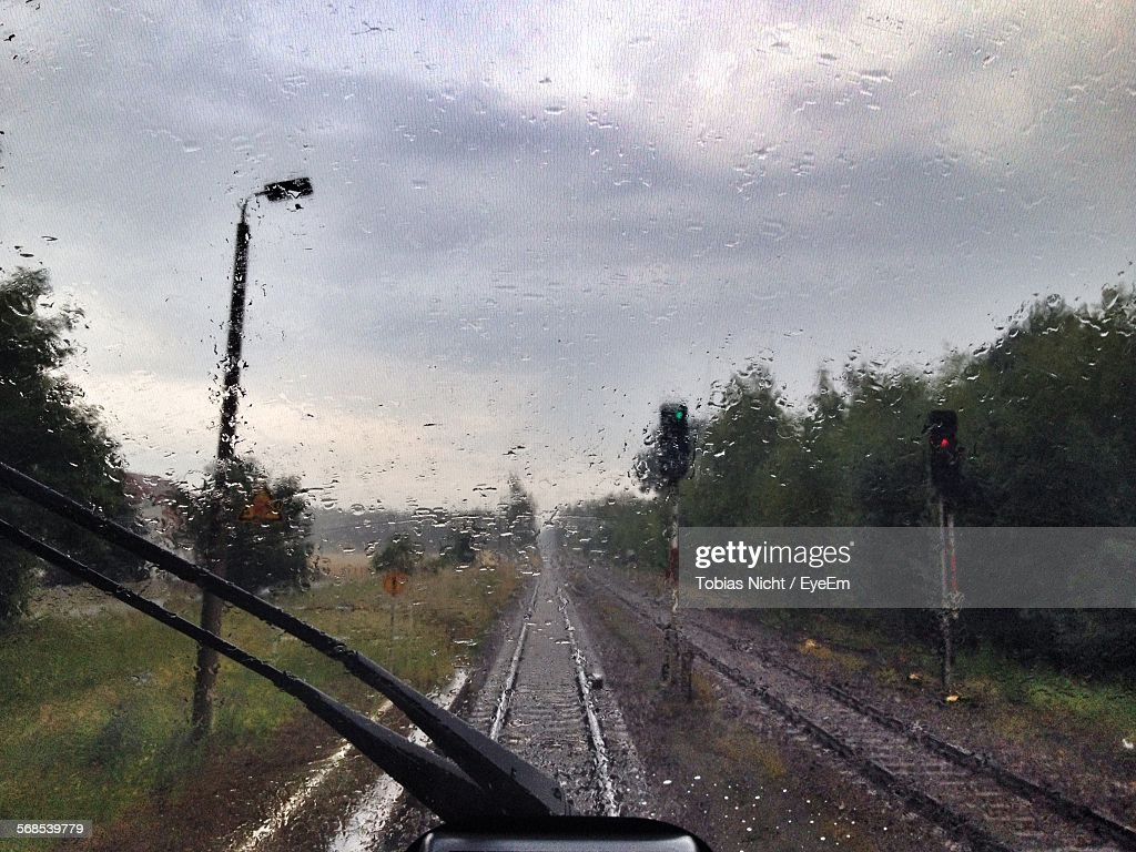Railroad Tracks On Field Against Sky During Monsoon Seen Through Train Windshield : Stock Photo