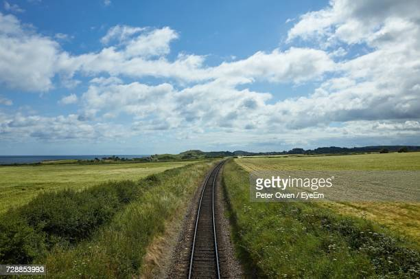 Railroad Tracks On Field Against Sky