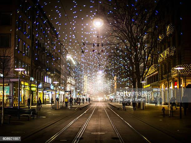 Railroad Tracks On Road Amidst Buildings In Illuminated City During Christmas