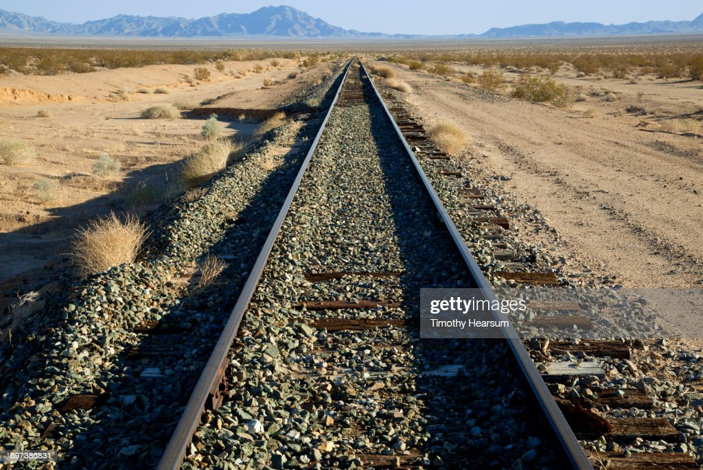 Railroad tracks passing through desert landscape : Stock Photo