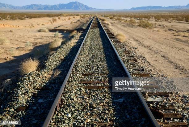 railroad tracks passing through desert landscape - timothy hearsum stock-fotos und bilder