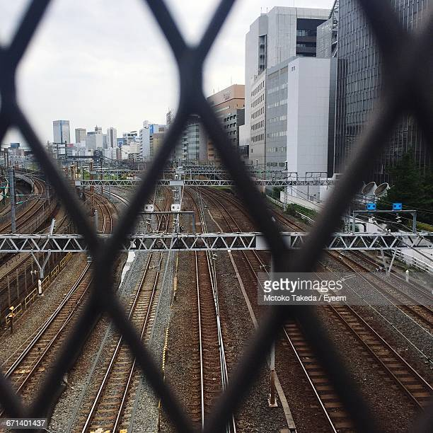 Railroad Tracks Seen Through Fence