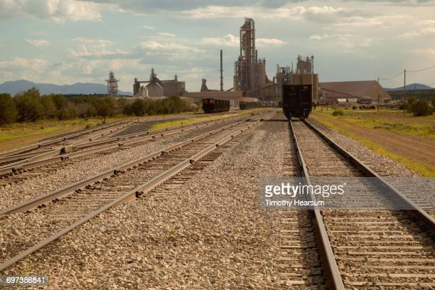railroad tracks with cement plant in background - timothy hearsum stock pictures, royalty-free photos & images