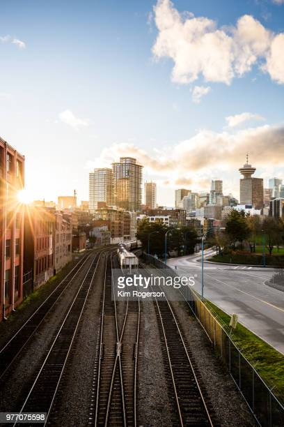 railroad tracks with sunburst await the transport trains into vancouver - east stock pictures, royalty-free photos & images