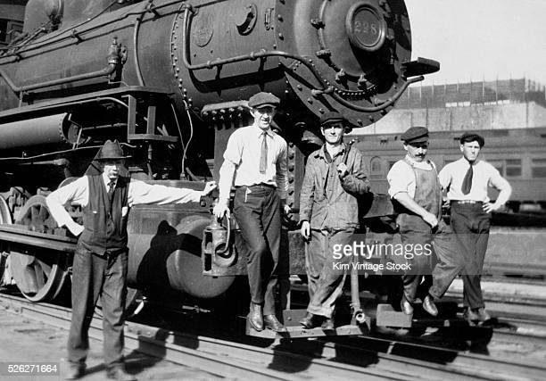 Railroad workers pose on the cow catcher of a Rock Island Line locomotive