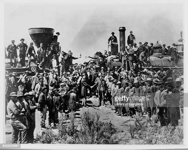 Railroad workers situated on and around two locamotives celebrate as two men shake hands signifying the joining of the Central Pacific and Union...