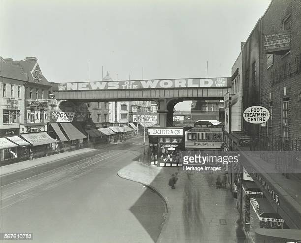 Railway bridge and advertising over the Brixton Road Lambeth London 1938 The News of the World is advertised on the railway bridge The row of shops...