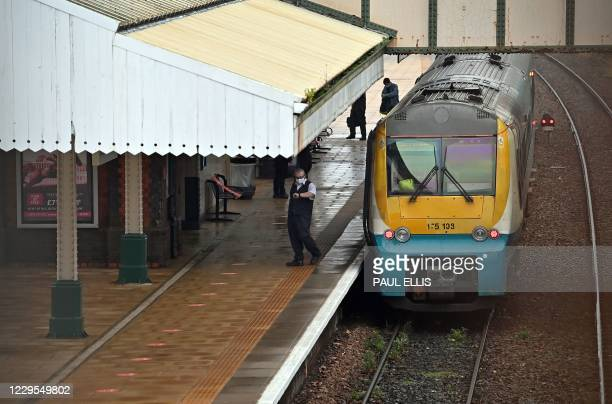Railway employee checks his watch on the platform before a train depart Wrexham General Station in North Wales on November 9, 2020 as Wales emerges...