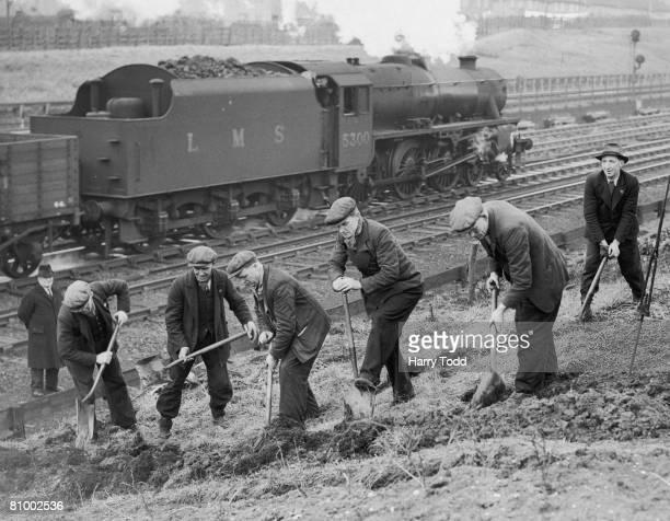 Railway employees create a vegetable patch beside a railway track near Harrow during World War II, 4th March 1940.