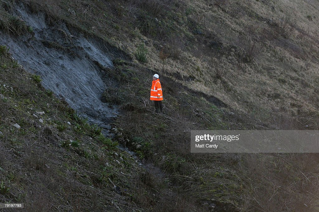 A railway engineer stands on a bank as inspection on the damage is inspected that was caused by a landslide on the London to South Wales train line near Chipping Sodbury, on January 24, 2008 in South Gloucestershire, United Kingdom. The closure of the line will bring major disruption to train services to Wales and the line is likely to be closed for several days while repairs are under taken.