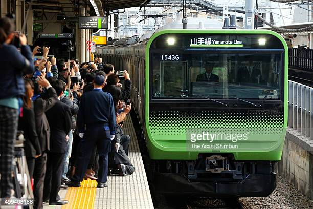 Railway fans take photographs of the JR East's new E235 series train on the Yamanote Line at Osaki Station on November 30 2015 in Tokyo Japan E235...