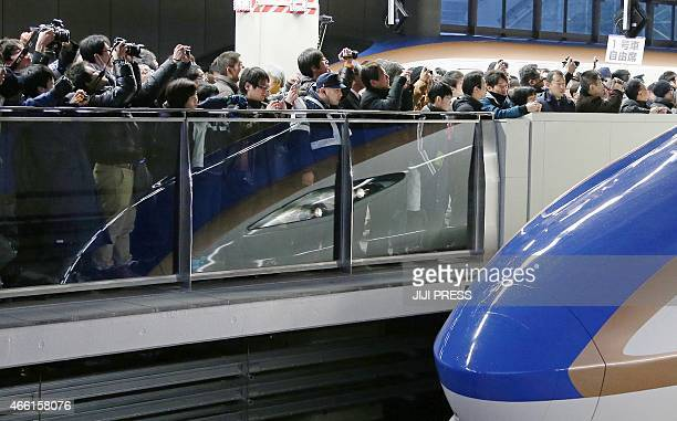 Railway fans welcome the first train of the new Hokuriku 'shinkansen' or bullet train bound for Tokyo at Kanazawa station in Ishikawa prefecture as a...