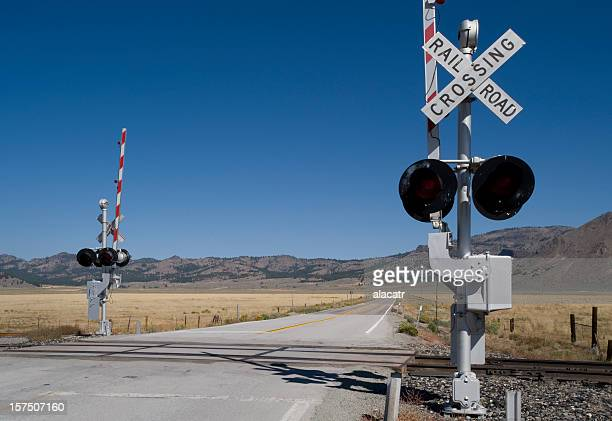 railway level crossing on both sides of extended road - railroad crossing stock pictures, royalty-free photos & images