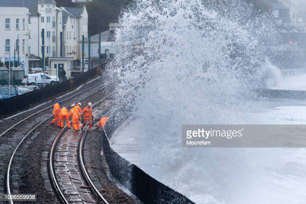 railway maintenance crew repairing railway track after storm damage - railings stock photos and pictures