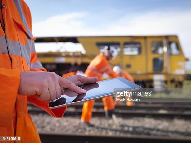 Railway maintenance worker using digital tablet, close up