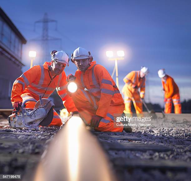 Railway maintenance workers inspecting track at night