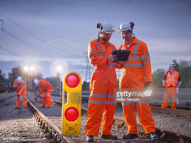 Railway maintenance workers using digital tablet at night