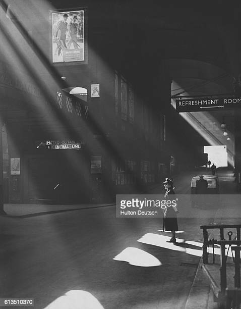 A railway policewoman stands in the warmth of a spring sun beam at the Liverpool Street Station in London