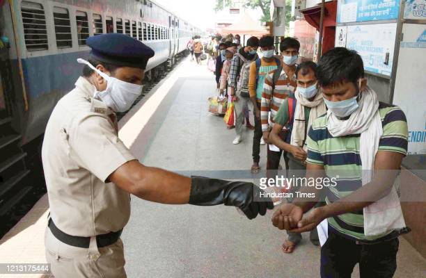 Railway Protection force personnel dispenses sanitizer to migrants who arrived from Rohtak on a Shramik Special at Danapur Station on May 14 2020 in...