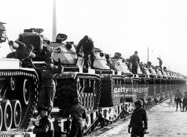 Railway servant and several US soldiers check the securing of the US tanks, which have been loaded on a train for transport at the train station...