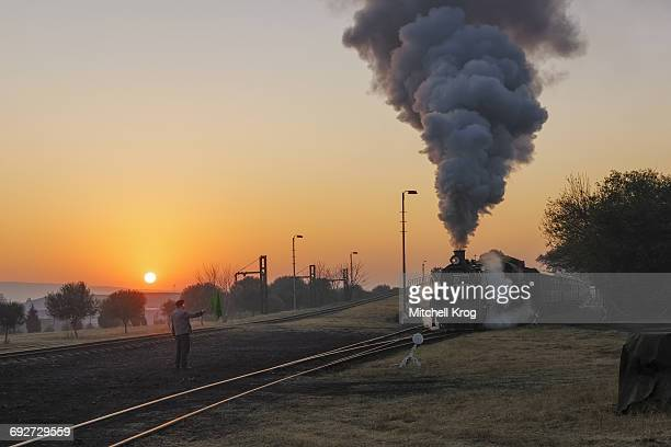 A Railway Signal Man at Sunrise Giving a Green Flag to a Locomotive Passenger Train to Begin its Journey. Pretoria, Gauteng Province, South Africa