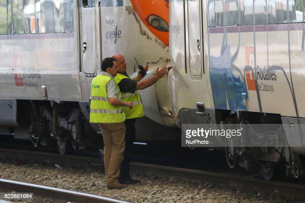 Railway technicians check a train wagon at the Estacio de Franca in central Barcelona on July 28 2017 after a regional train appears to have hit the...