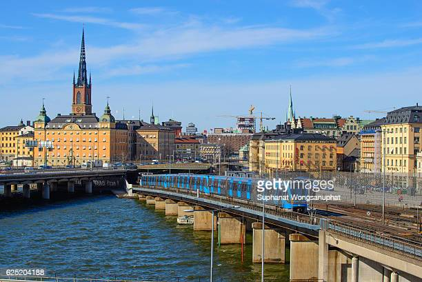 Railway tracks and trains near Stockholm's main train station in Norrmalm area, Stockholm. Cathedral in background. Square composition.