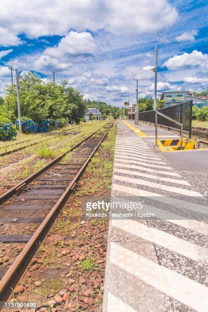Railway Tracks At Station Against Cloudy Sky