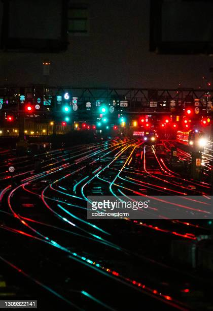 railway tracks illuminated at night in the city - direction stock pictures, royalty-free photos & images