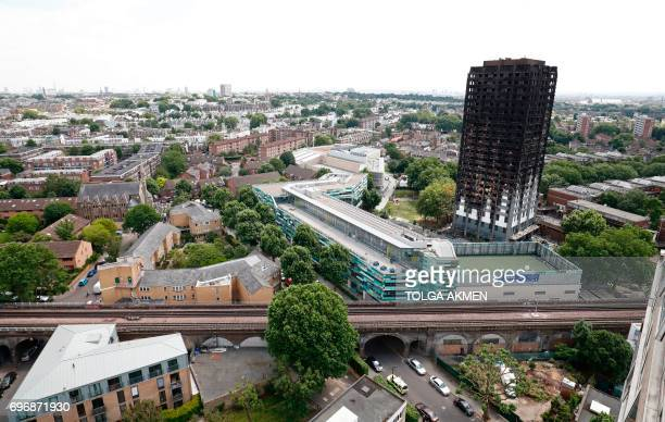 Railway tracks run in front of the charred remains of the Grenfell Tower block in Kensington west London on June 17 following the June 14 fire at the...