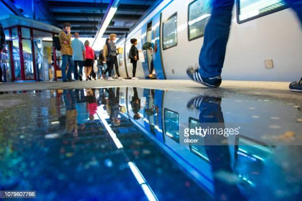 railway station perron en pendelaars in regen - spitsperiode stockfoto's en -beelden