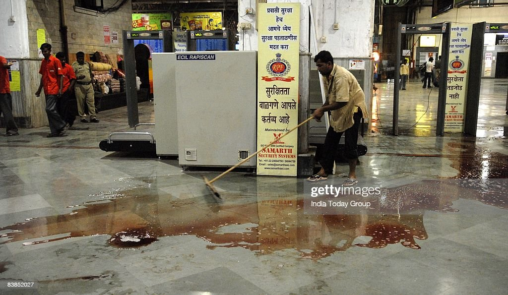 A railway worker clears the CST station floor where the terrorist attack took place on November 26, 2008 in Mumbai, India. Following terrorist attacks on three locations in the city which have left over 140 people dead, troops are now working to free the remaining hostages being held inside the Taj Mahal Palace Hotel.