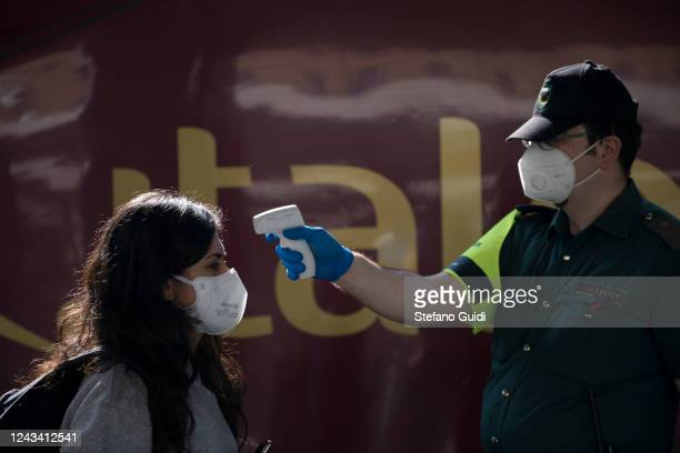 A railway worker measures the temperature of a traveller wearing a protective mask before boarding a train at the Porta Nuova railway station on June...