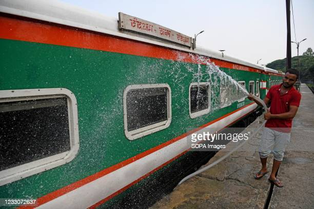 Railway worker seen washing a train at Komlapur railway station as the train service prepares to resume. The intercity train will resume operations...