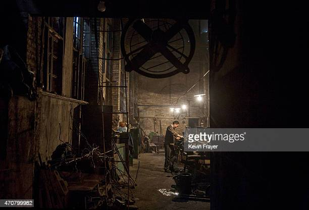 A railway worker services parts for a coal powered steam engine in the workshop on March 27 2015 at a station in the town of Shixi Sichuan Province...