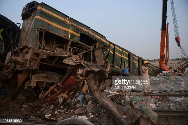 Railway worker stands at the site of a train accident in Daharki area of the northern Sindh province on June 7 as at least 43 people were killed and...