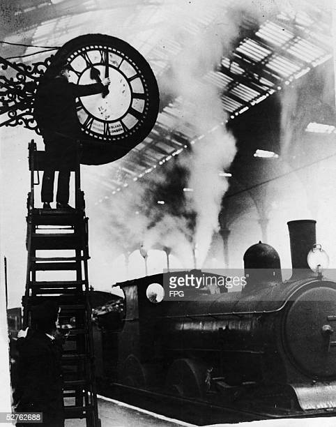 A railway worker stands on a ladder and changes a clock ahead one hour to begin Daylight Savings time at Liverpool Street Station London early 20th...
