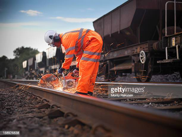 Railway worker using grinder to work on railway tracks