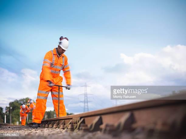 Railway worker using tool to work on railway tracks