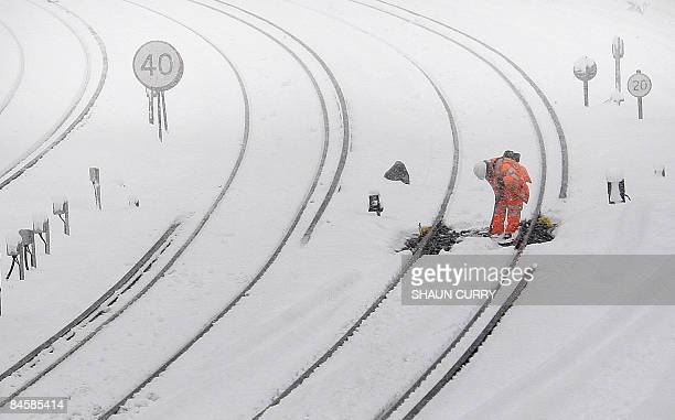 A railway worker walks along a snow covered track leading to London's Victoria station in central London on February 2 2009 A blanket of snow covered...