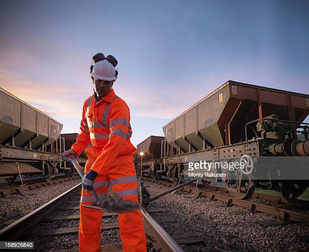 Railway worker with spade working on railway tracks at night